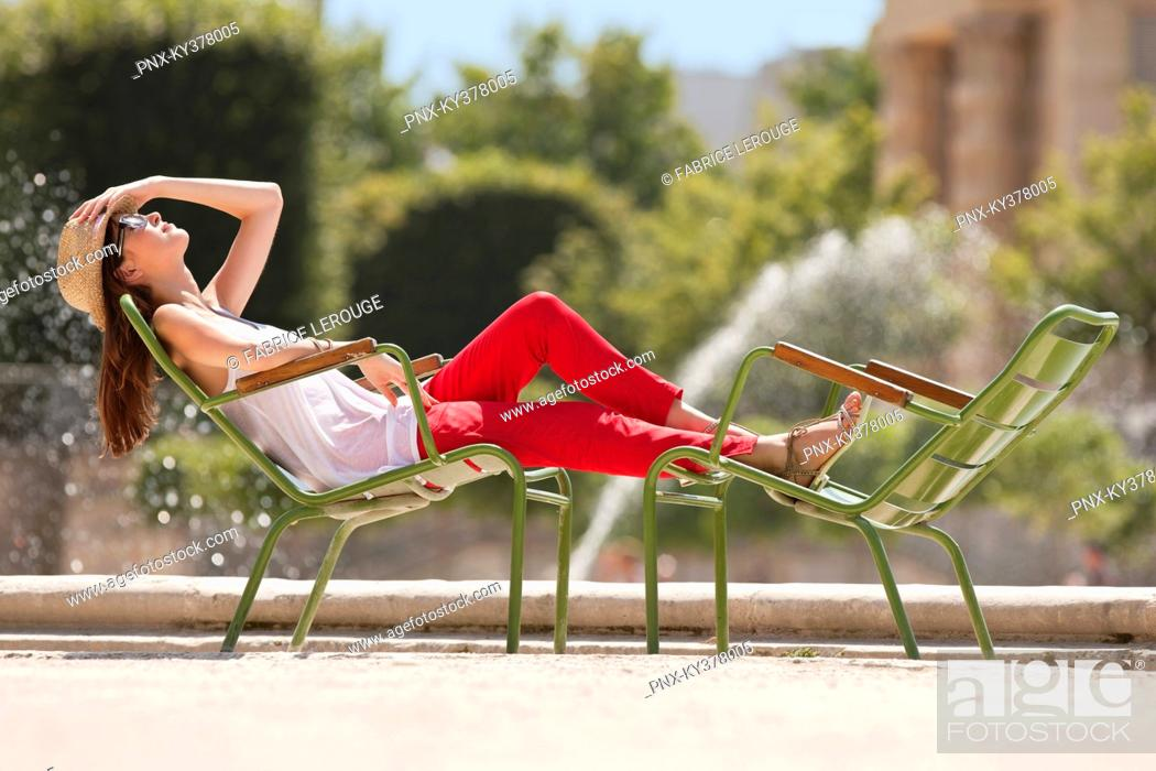 Stock Photo: Woman resting in a chair near a pond, Bassin octogonal, Jardin des Tuileries, Paris, Ile-de-France, France.