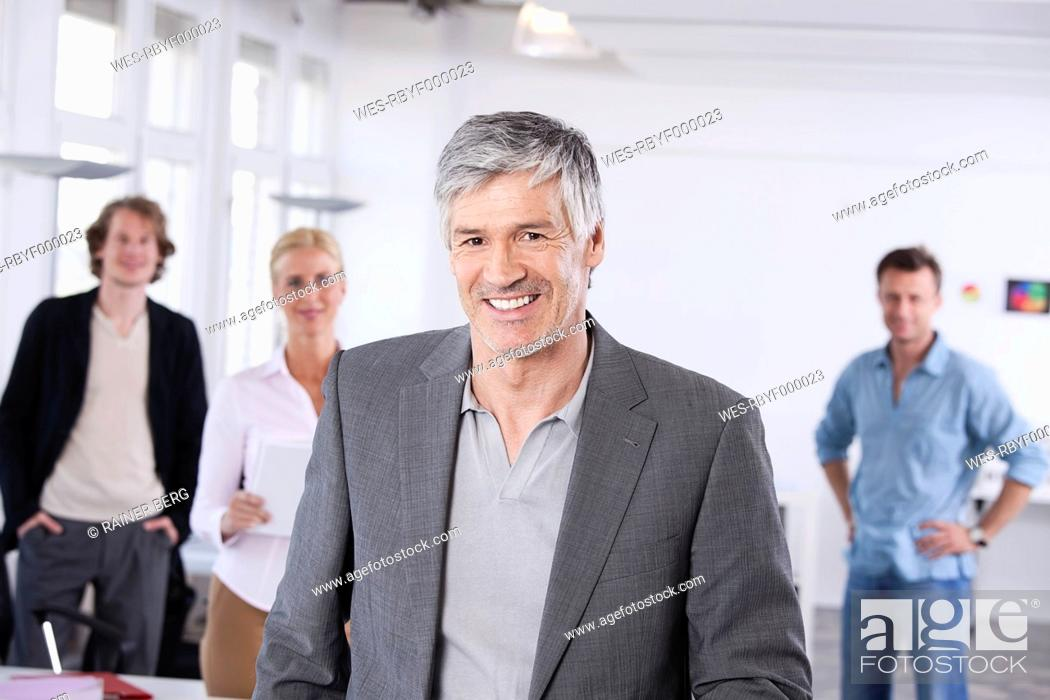 Stock Photo: Germany, Bavaria, Munich, Men and woman in office, smiling, portrait.