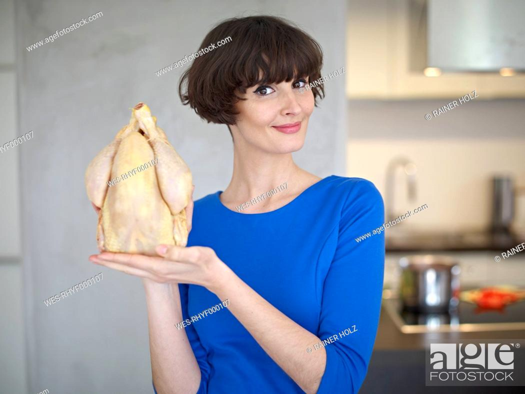 Stock Photo: Germany, Cologne, Young woman with raw chicken in kitchen, smiling, portrait.