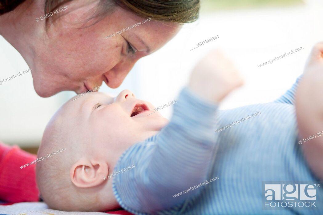Stock Photo: Mother kissing baby boy, Munich, Bavaria, Germany.