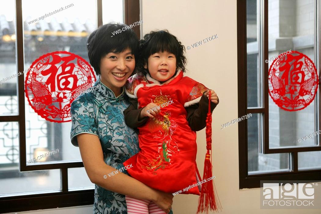 Stock Photo: Chinese mother holding her daughter looking at camera smiling.