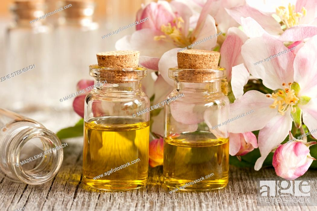 Stock Photo: Two bottles of essential oil with apple blossoms in the background.
