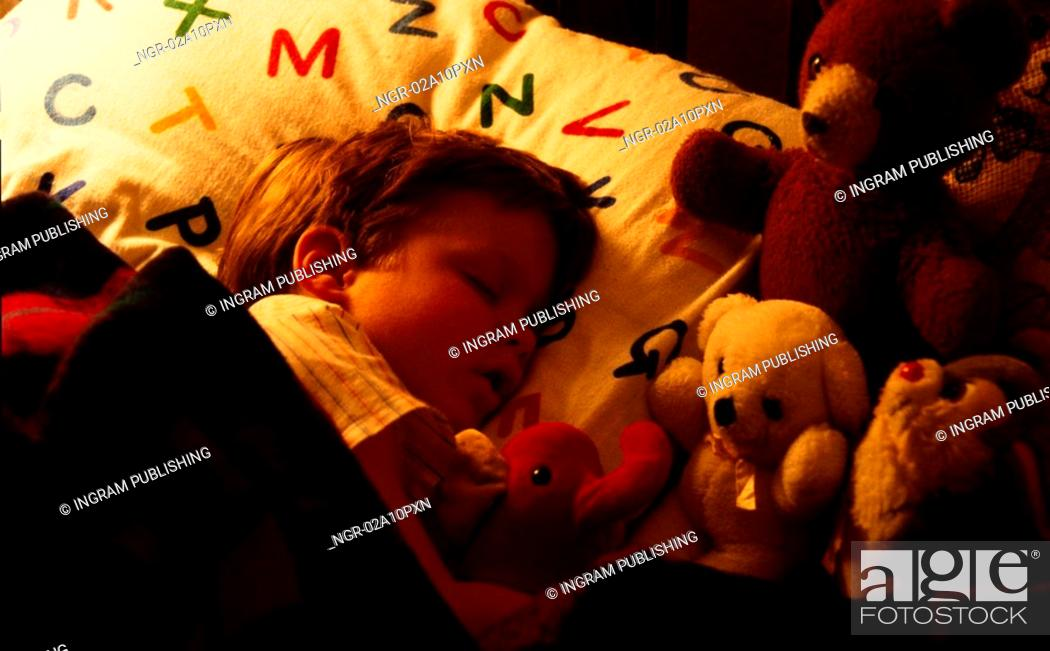 Stock Photo: Little boy sleeping with his toys.