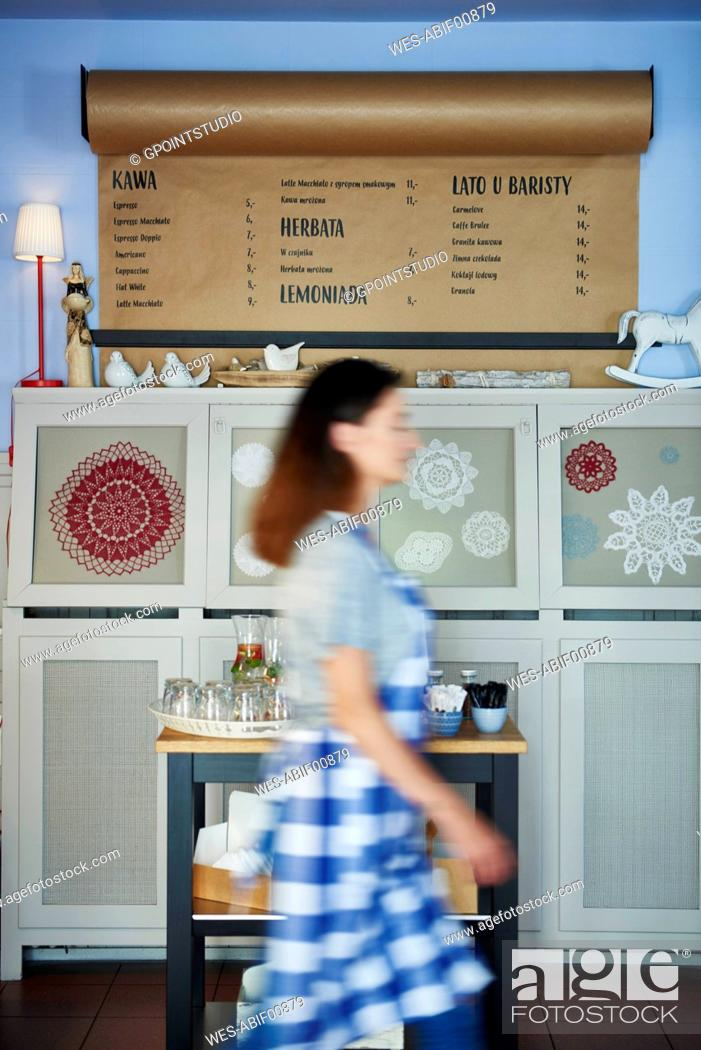Stock Photo: Waitress walking past drinks menu in a cafe.