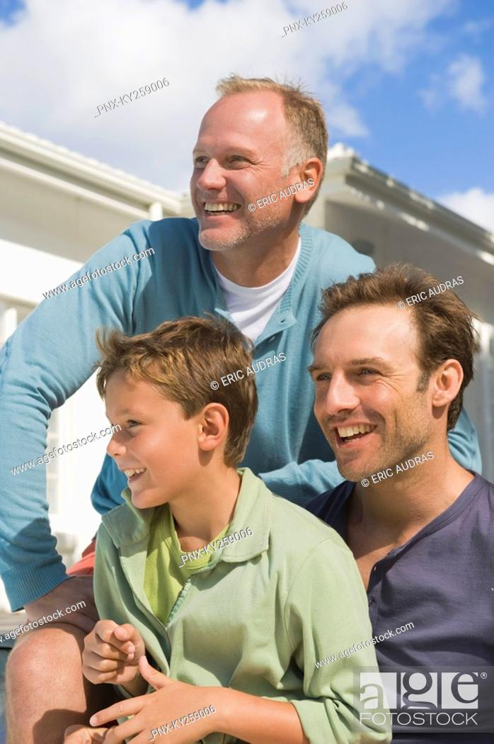 Stock Photo: Two men smiling with a boy.
