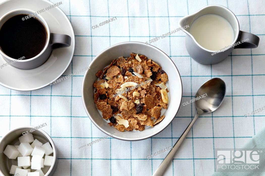 Stock Photo: Cereal with dried fruit, coffee and milk jug, overhead view.