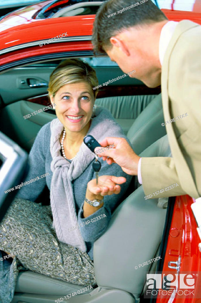 Stock Photo: Car salesman giving the car keys to a mid adult woman.