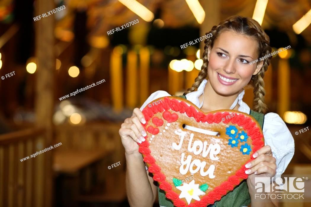 Stock Photo: Young woman holding Gingerbread heart at Oktoberfest, Munich, Germany.