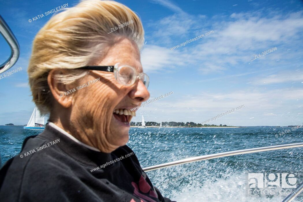 Stock Photo: Caucasian retired senior, mature woman having fun and laughing during an outing on the boat in the ocean, in Brittany, France.