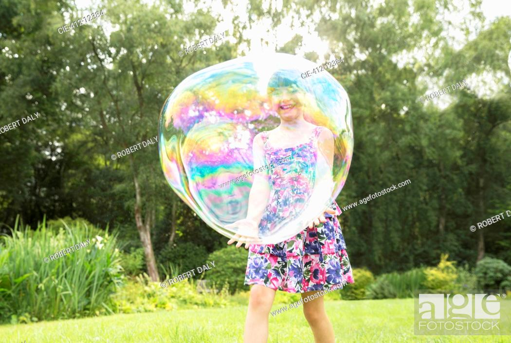 Imagen: Father and daughter playing with large bubbles in backyard.