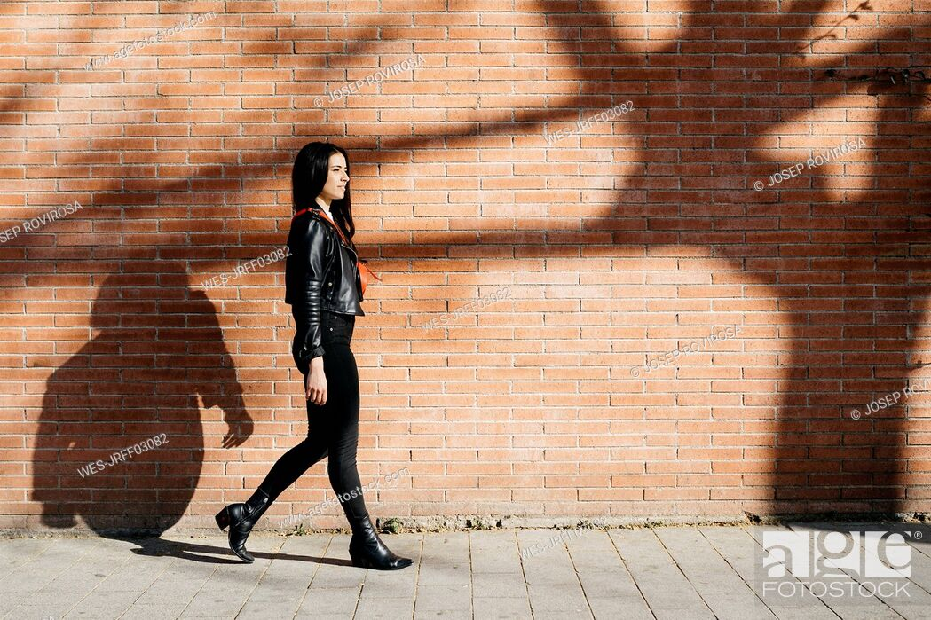 Stock Photo: Young woman with a red bag walking in front of a brick wall and a shadow of tree.