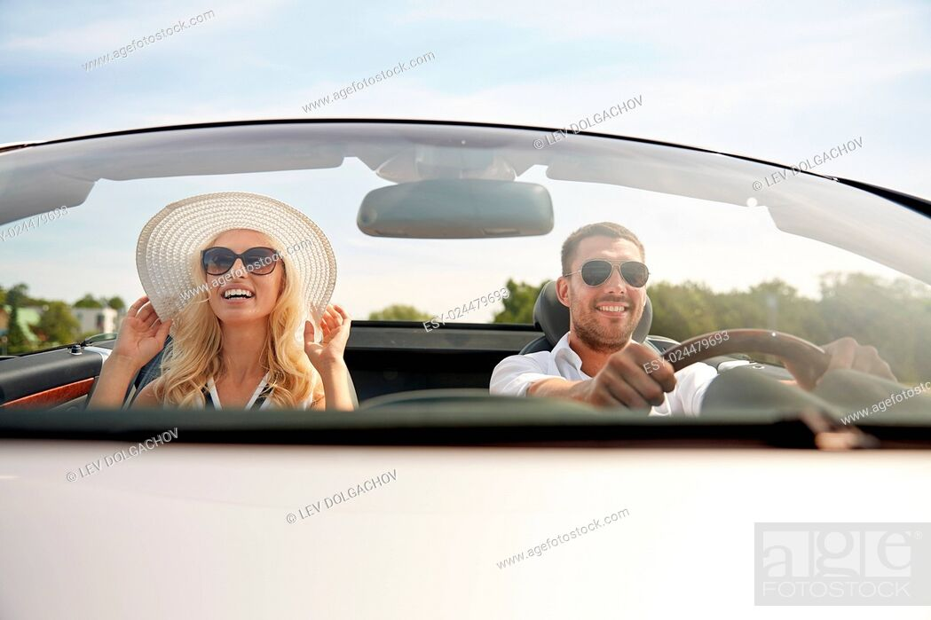 Stock Photo: road trip, travel, dating, couple and people concept - happy man and woman driving in cabriolet car outdoors.