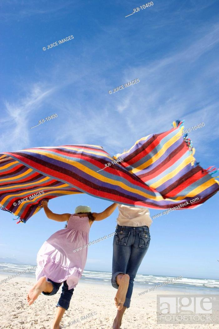 Stock Photo: Mother and daughter 5-7 holding up blanket on beach, rear view.