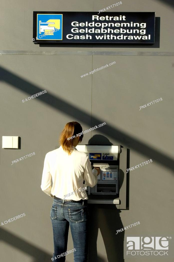 Stock Photo: Rear view of a businesswoman using an ATM.