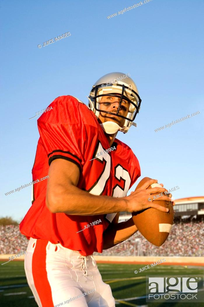 Stock Photo: Quarterback with football looking downfield.