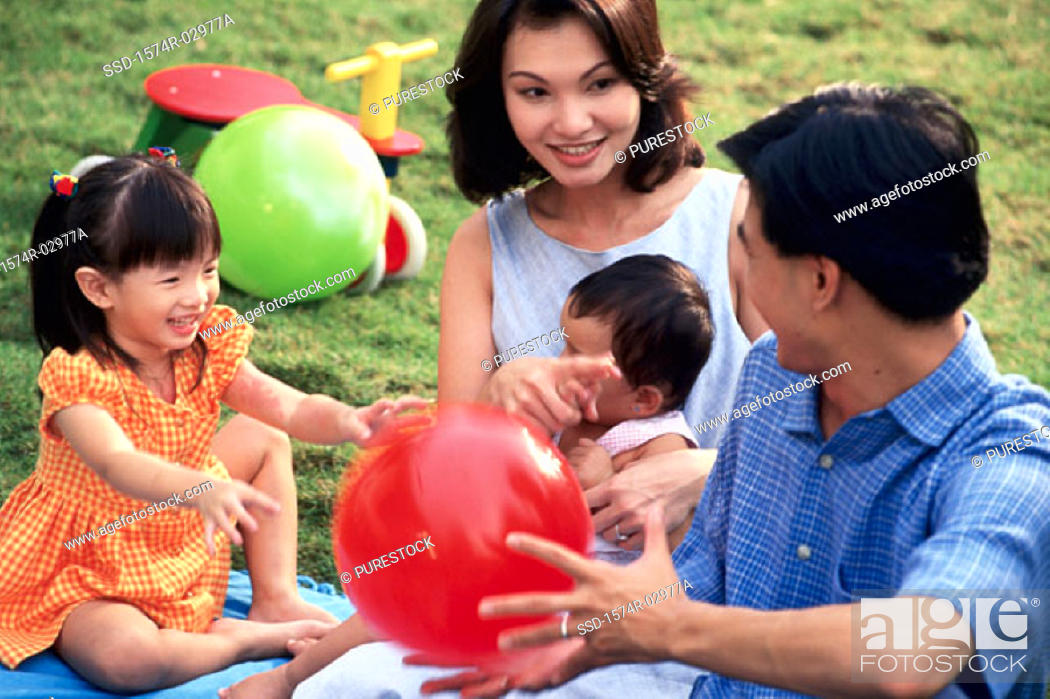 Stock Photo: Parents sitting with their son and daughter on a lawn.