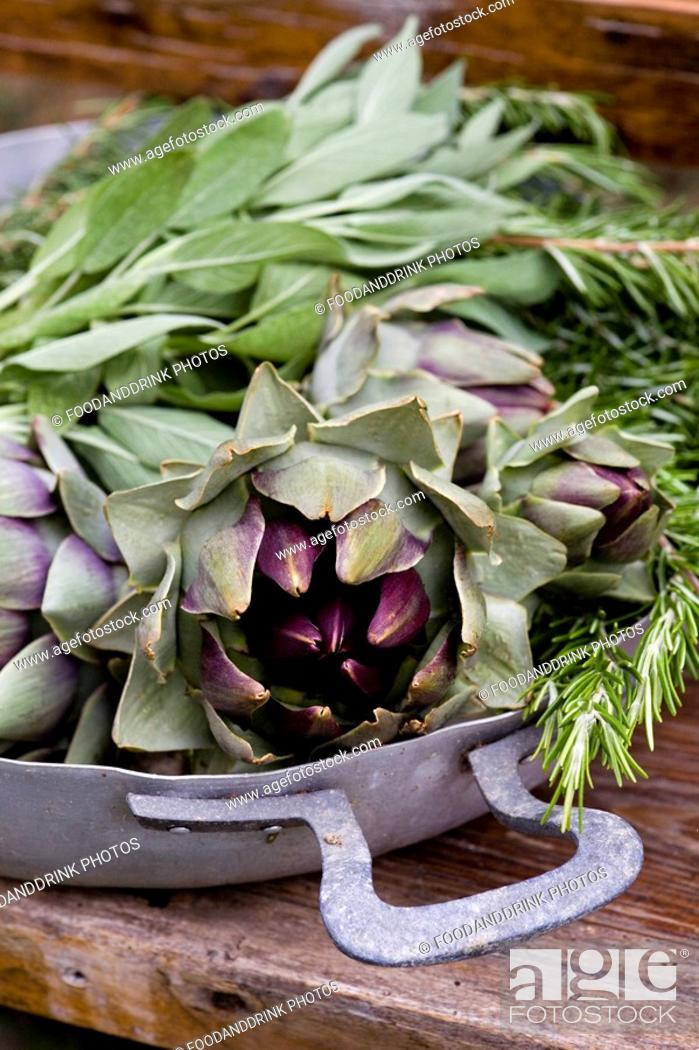 Stock Photo: Vegetables and herbs in metal basket on wooden table.