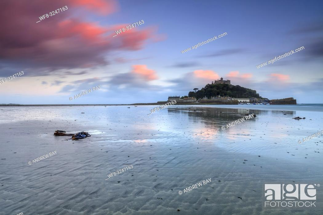 Stock Photo: St Michael's Mount captured at sunset from Marazion Beach in Cornwall. A long shutter speed was utilized to blur the movement in the clouds.