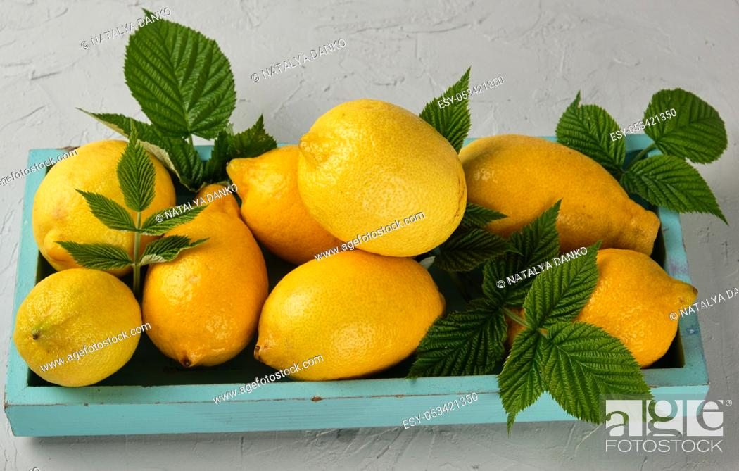 Stock Photo: fresh ripe whole yellow lemons on a blue wooden board, ingredients for making summer drinks, top view.