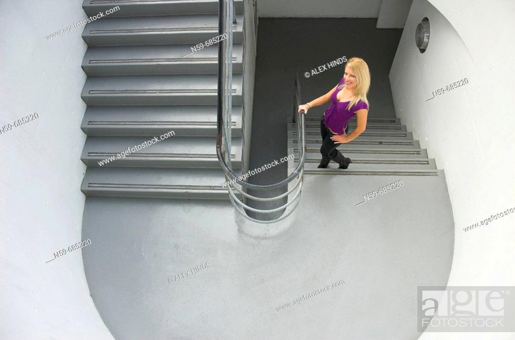 Stock Photo: Young blonde woman on stairs.