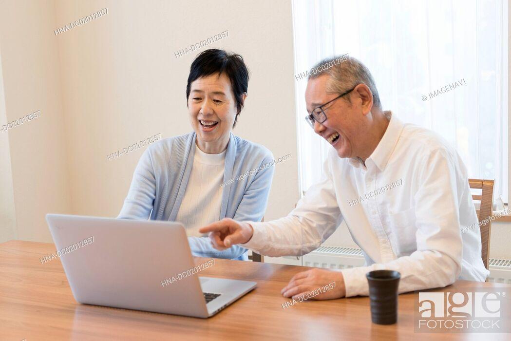 Stock Photo: Senior couple using laptop together.