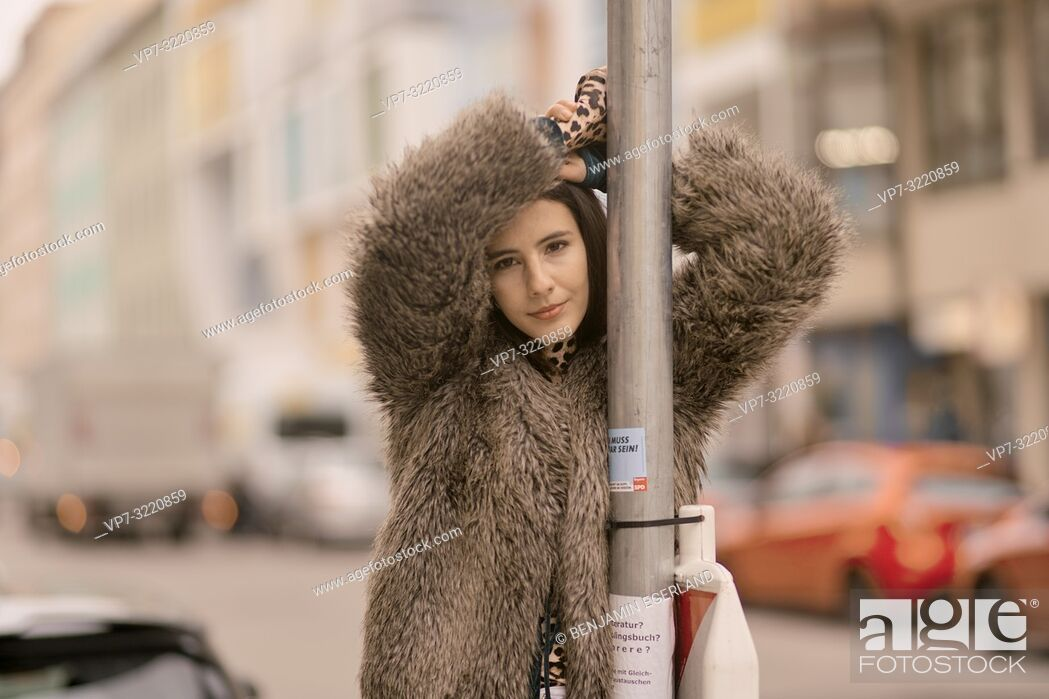 Stock Photo: young woman leaning on traffic sign at street in city, relaxed mood, in Munich, Germany.