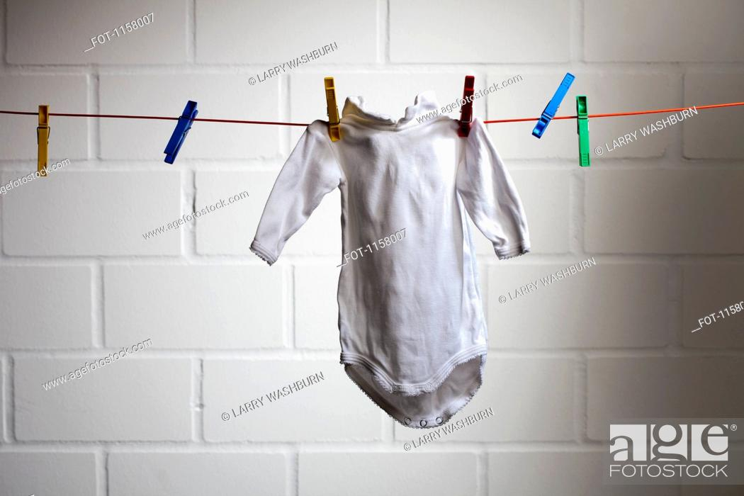 Stock Photo: A baby's onesie hanging from a clothesline.