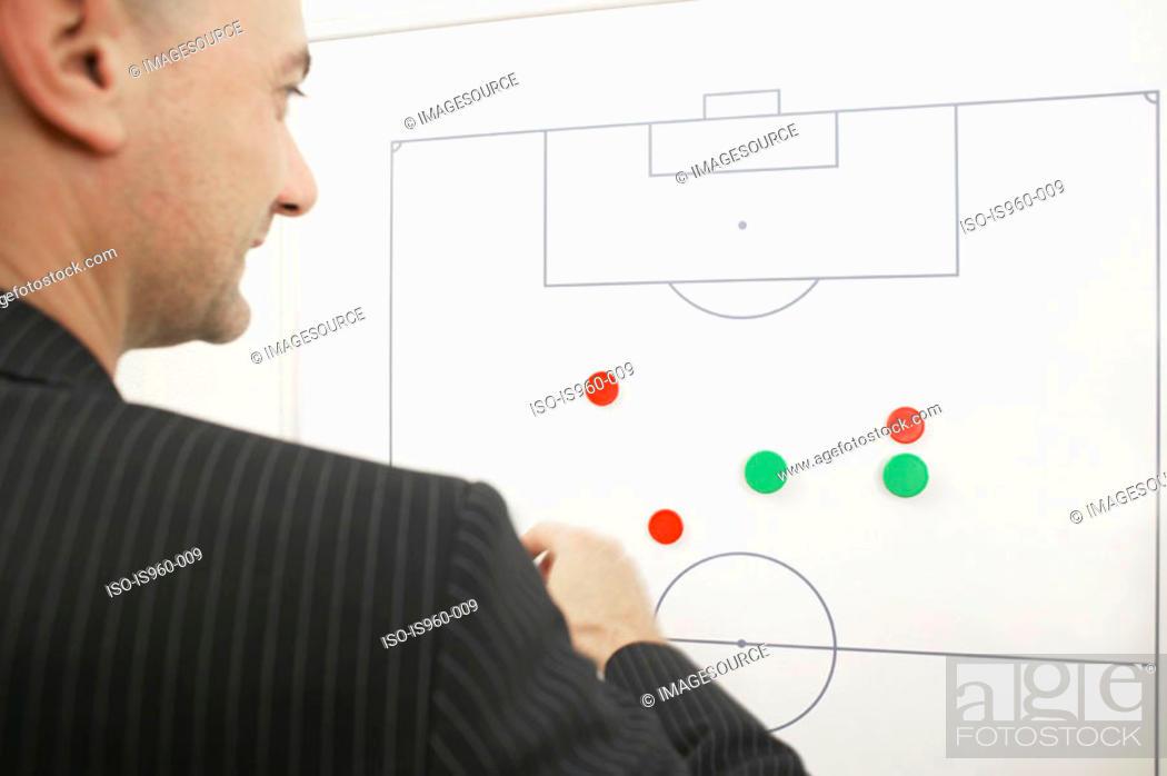 Stock Photo: Football coach thinking of strategy.