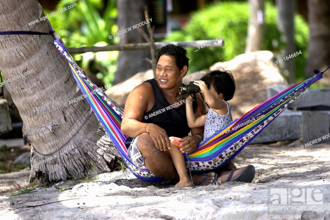 Stock Photo: Man and young girl with binoculars sit in hammock Hat Sai Ri beach Ko Tao island Thailand.