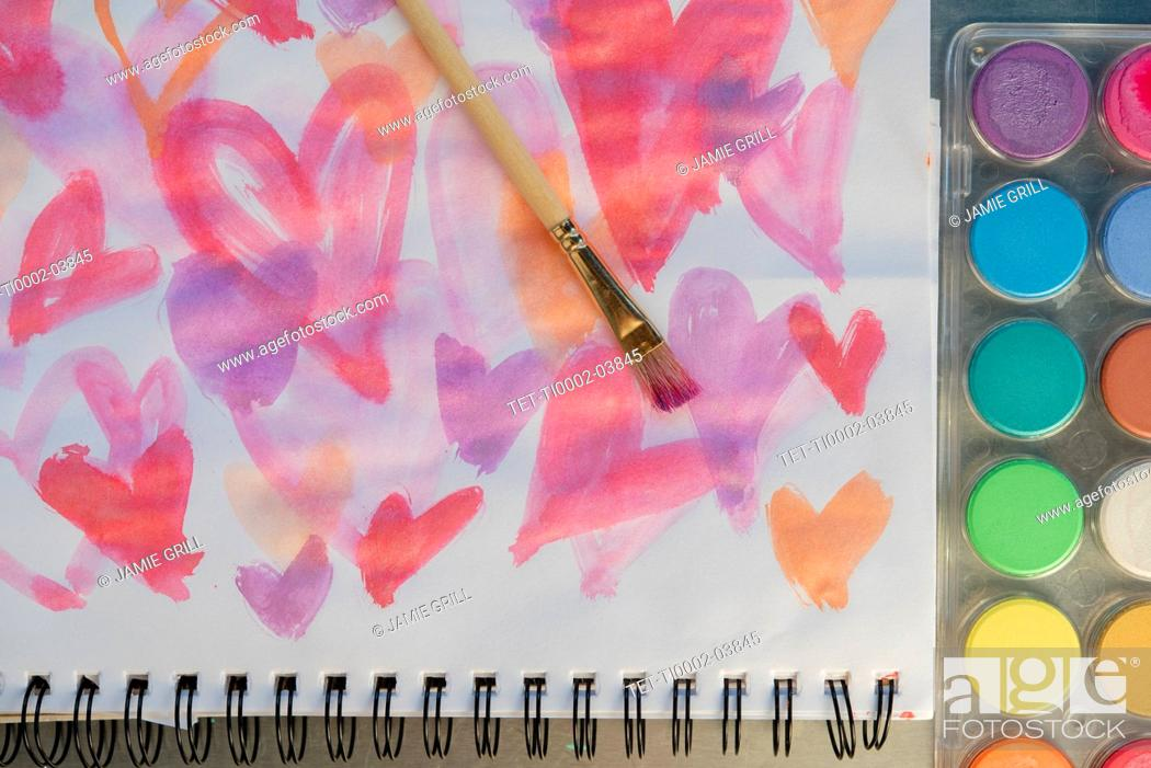 Stock Photo: Paintbrush on watercolor painting of hearts by paints.