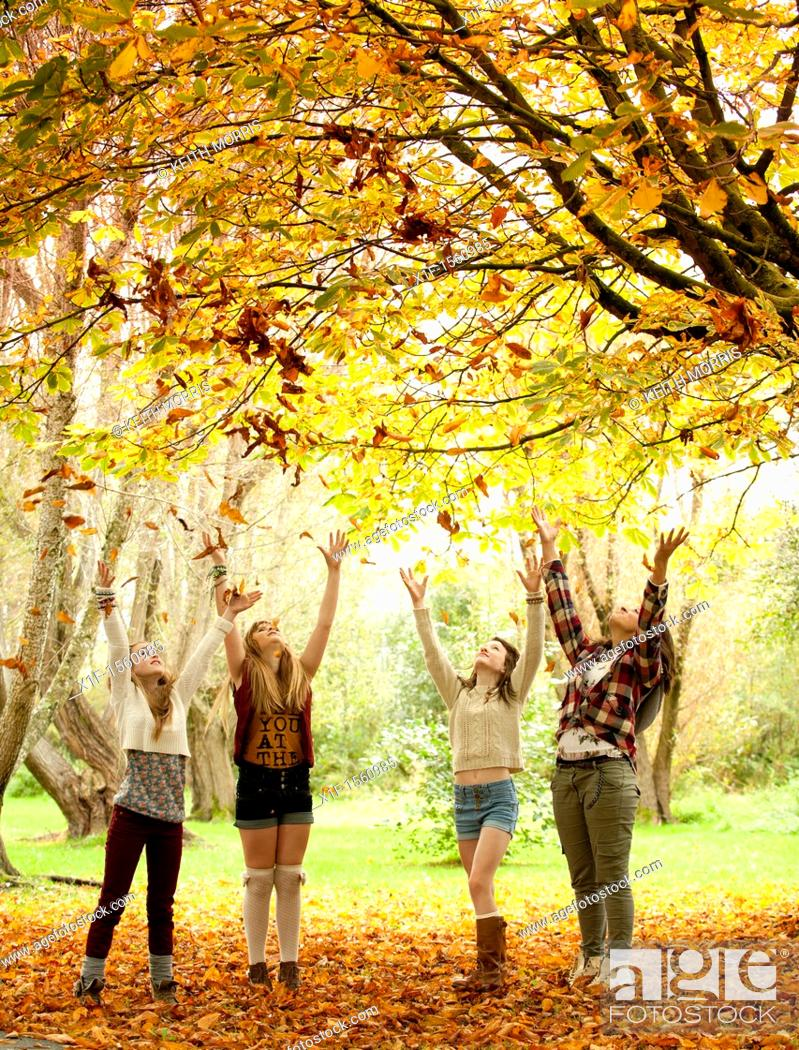 Stock Photo: A group of 13 year old teenage girls, throwing leaves into the air, autumn morning, UK.