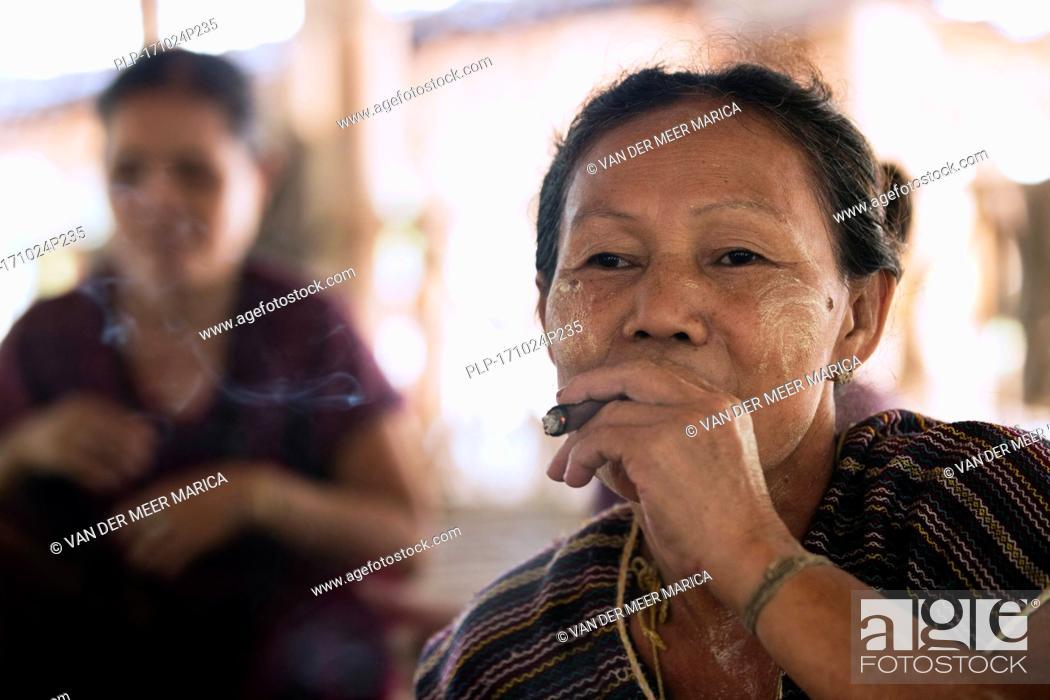 Stock Photo: Old Burmese woman of the Bamar tribe wearing thanaka and smoking a cigar in Kayin village near Hpa-an, Kayin State / Karen State, Myanmar / Burma.