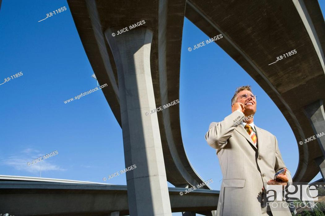 Stock Photo: Businessman using mobile phone beneath overpasses, low angle view.