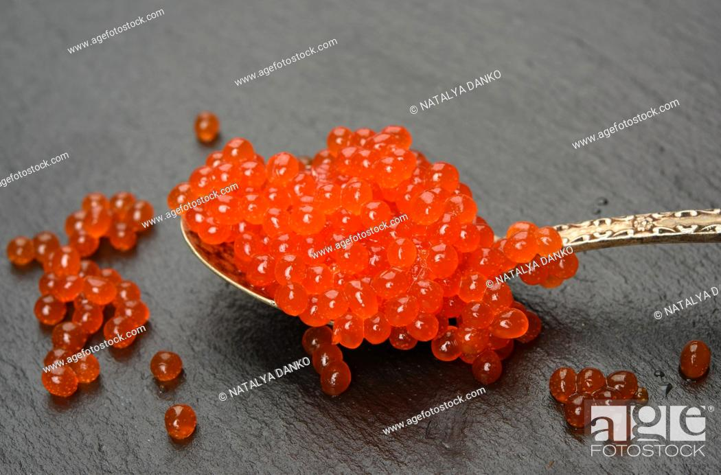 Stock Photo: red caviar of chum salmon in a metal spoon on a black background, close up.