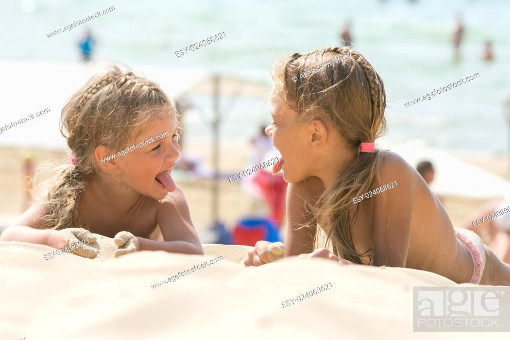 Stock Photo: Two happy little girls show each other tongues on a sandy beach.