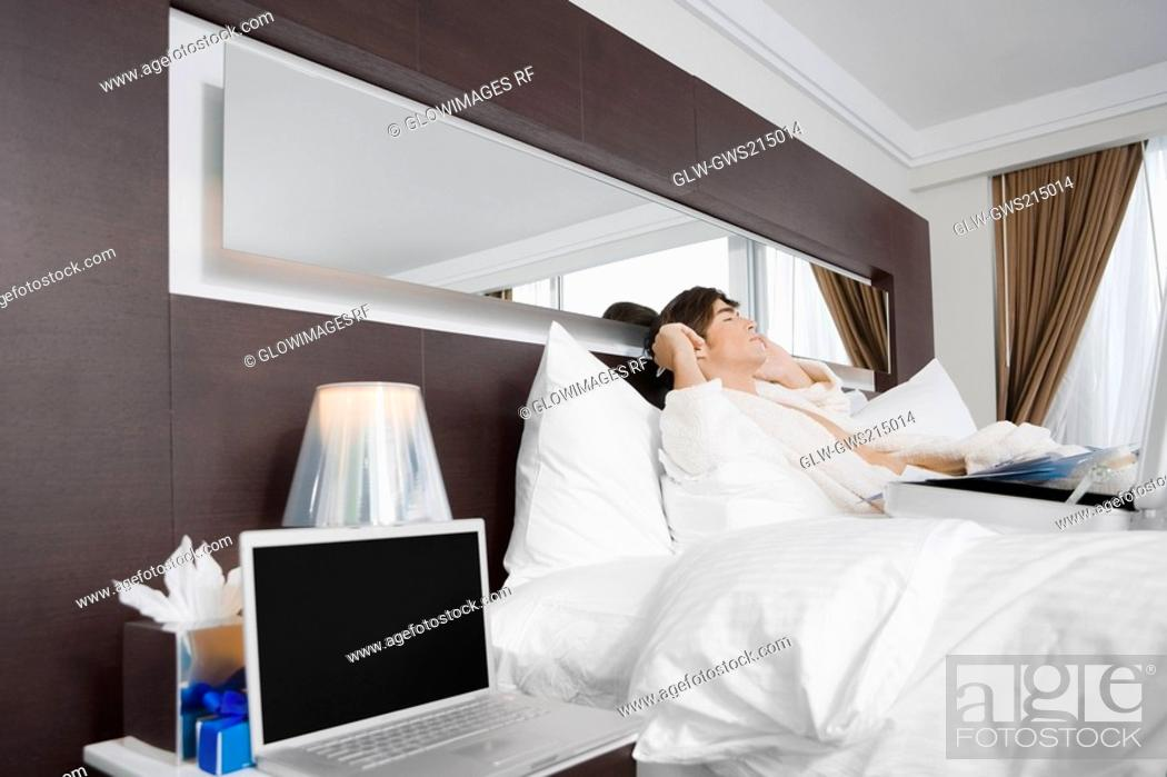 Stock Photo: Young man lying on the bed and talking on a mobile phone.