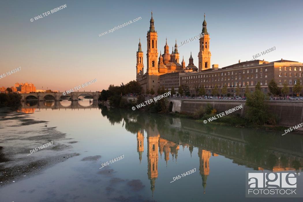 Stock Photo: Spain, Aragon Region, Zaragoza Province, Zaragoza, Basilica de Nuestra Senora de Pilar on the Ebro River, sunset.