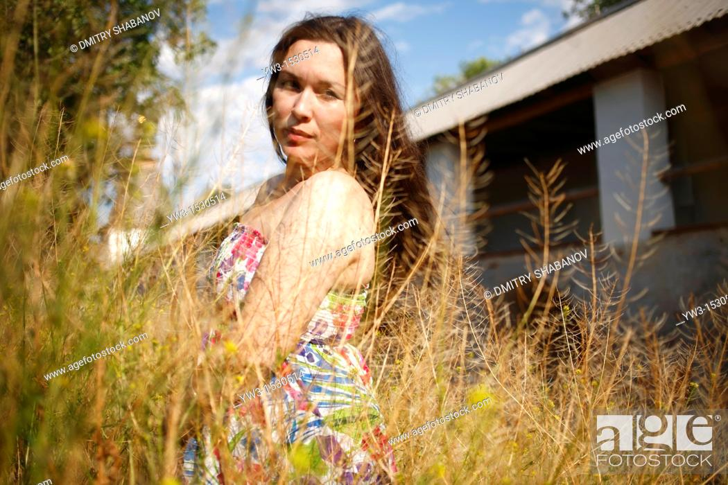Stock Photo: brunette women 25-30 years staying in the yellow grass against old gallery building.