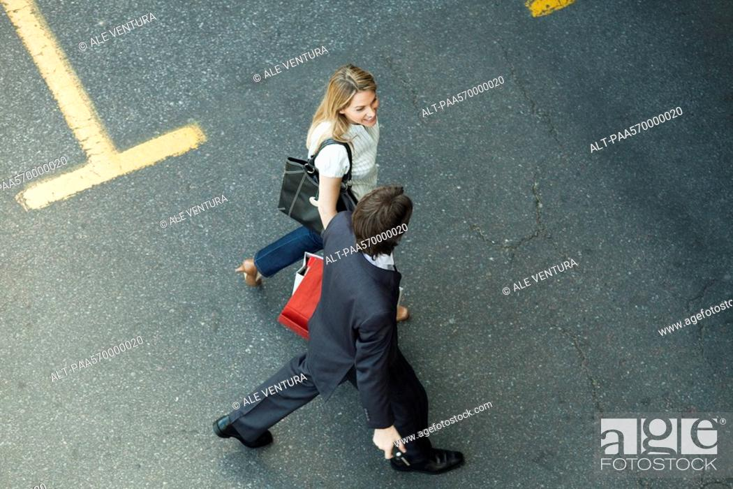 Stock Photo: Couple walking together across parking lot, woman carrying shopping bags.