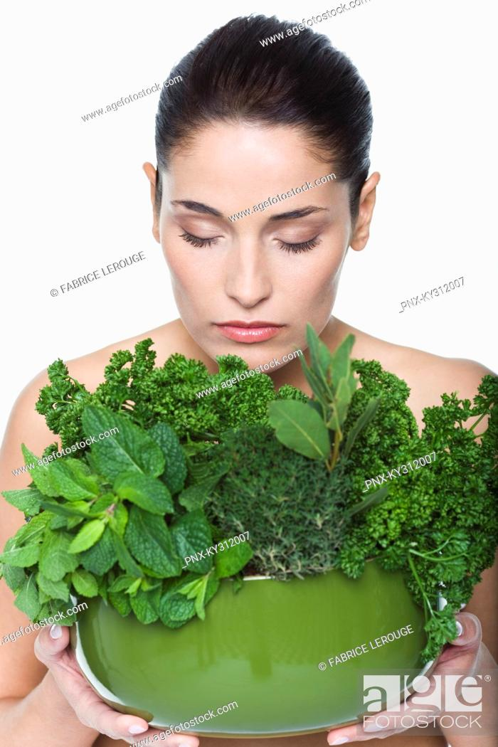 Stock Photo: Young woman holding fresh herbs.