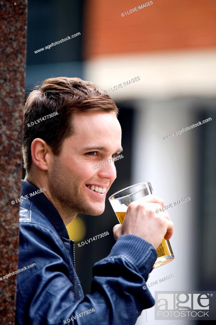 Stock Photo: A young man drinking a pint of beer.