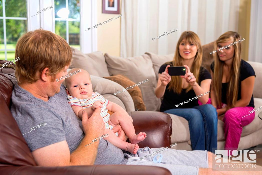 Stock Photo: Father with baby boy and two young women in background taking picture with smart phone camera.