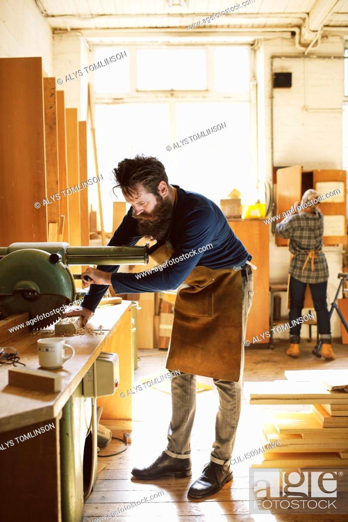 Imagen: Mid adult craftsman using machinery in organ workshop.