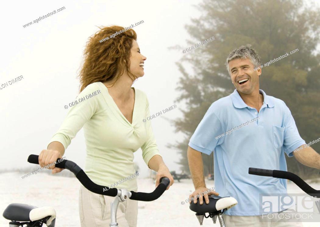 Stock Photo: Mature couple walking with bikes on beach.