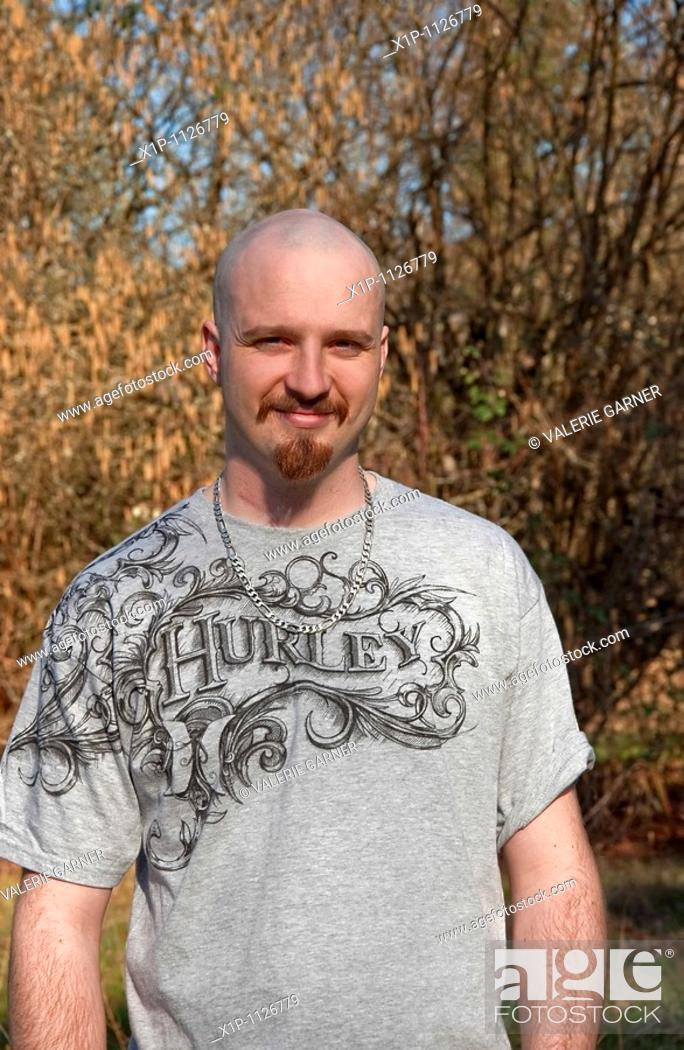 Stock Photo: This vertical portrait of a mid-twenties Caucasian man, smiling outdoors in early spring He has light skin and a warm smile, a goatee with his head shaved bald.