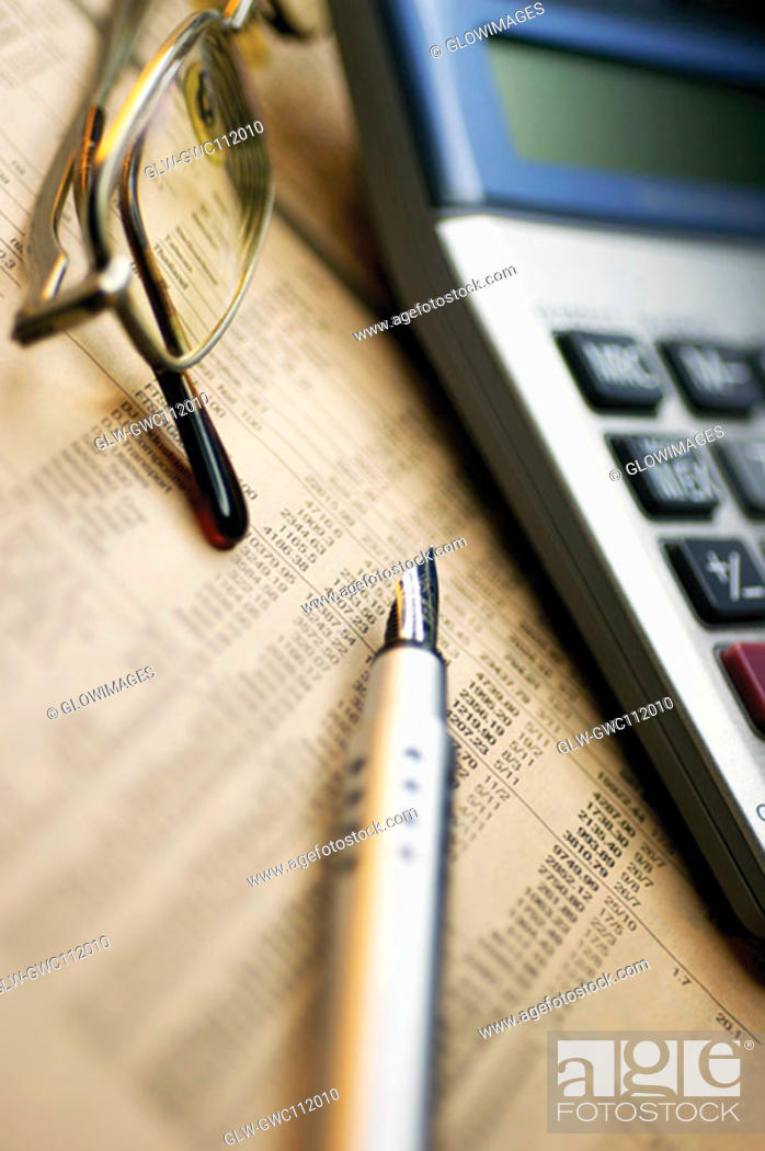 Stock Photo: Close-up of a fountain pen with a calculator and eyeglasses on a financial page.