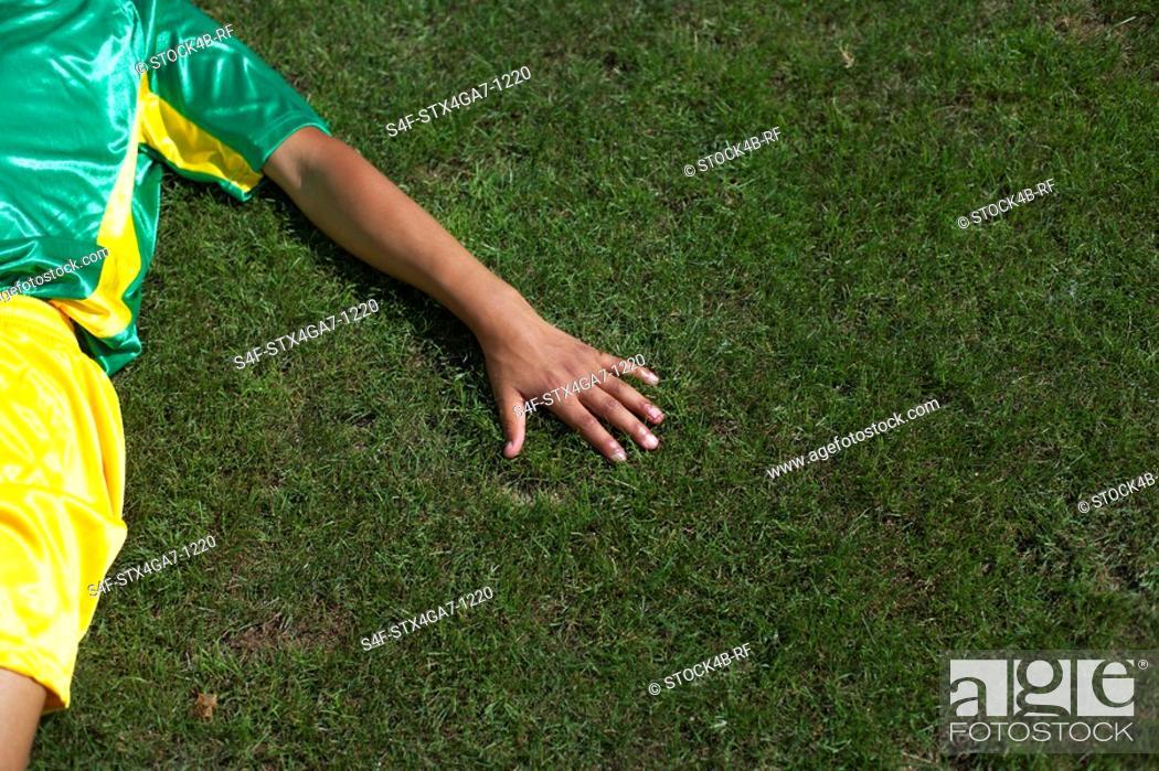Stock Photo: Brazilian kicker lying on grass.
