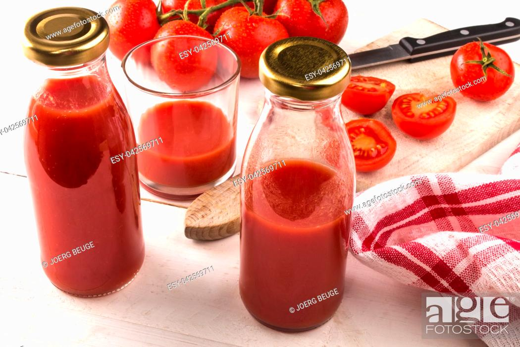Stock Photo: home made organic tomato juice in a glass and bottle.