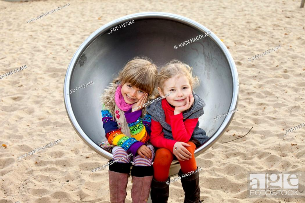 Stock Photo: Two girls sitting on spherical metal chair in park.