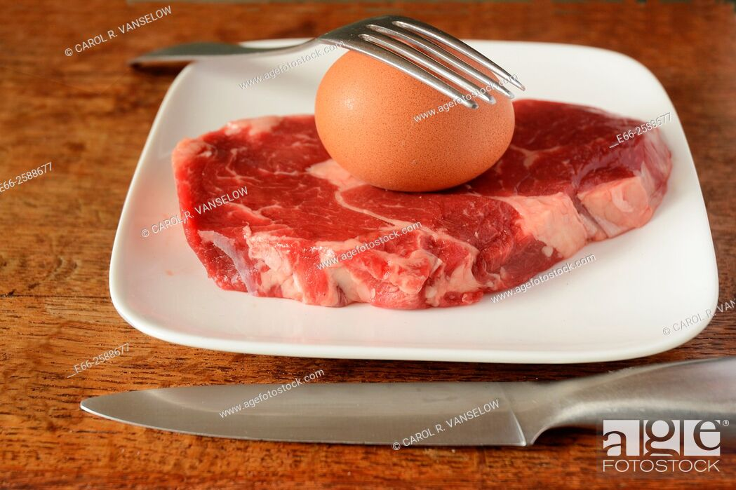 Stock Photo: Whole brown egg in shell and ribeye steak on white plate with knife and fork. Eggs and meats are integral parts of the Paleo Diet.